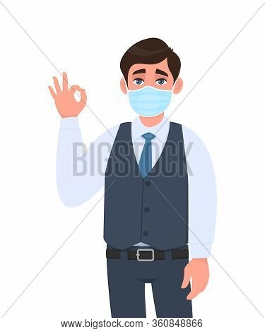 Young Business Man Wearing Medical Mask And Showing Okay, Ok Sign. Trendy Person In Waistcoat Coveri