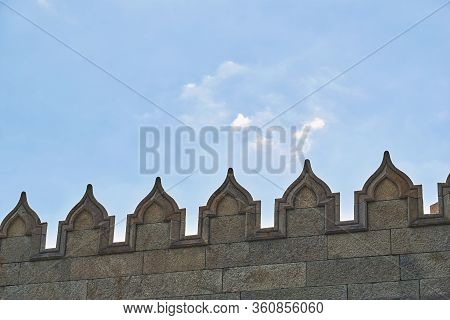 Upper Jagged Part Of The Stone Wall Of An Ancient Fortress Or Castle Against A Clear Sky Closeup