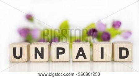 Unpaid - Financial Business Concept. Wooden Cubes On A White Table. In The Background Are Pink Purpl