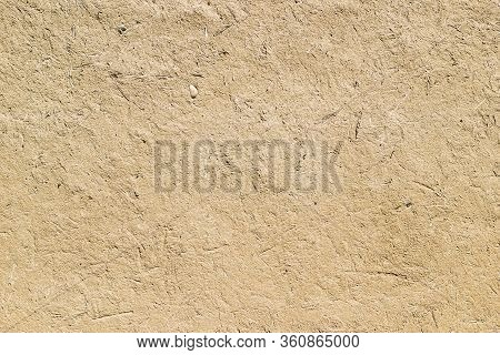 Adobe - Clay And Straw Material Weathered Wall Of Rural Old Country House Close-up As Clay Backgroun