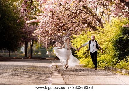 Cheerful Newlyweds Running Around The City Happy Among The Flowering Trees. Newlyweds Have Fun Spend