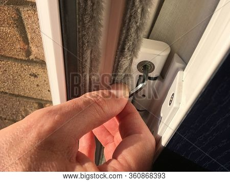 Person Making An Adjustment To A Composite Door Hinge With An Allen Key
