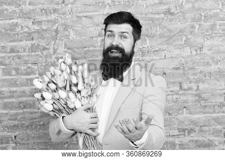 Romantic Gift. Macho Getting Ready Romantic Date. Tulips For Sweetheart. Man Well Groomed Tuxedo Bow