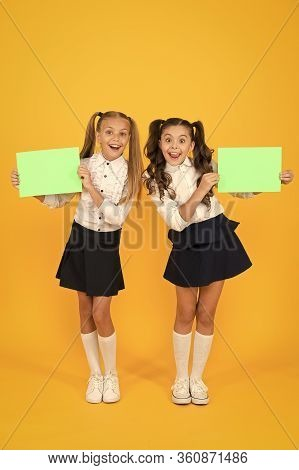 Presenting Product. Happy Little Girls Holding Blank Green Papers For Product Advertising On Yellow