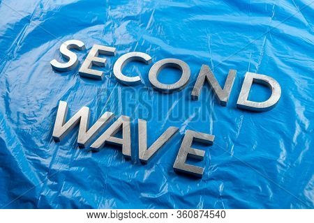 The Words Second Wave Laid With Silver Metal Letters Over Crumpled Blue Plastic Film Background With