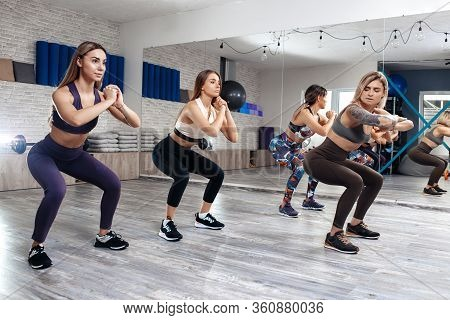 Group Of Four Young Motivated Girls Doing Squats In Fitness Class. Sport, Fitness And Lifestyle Conc