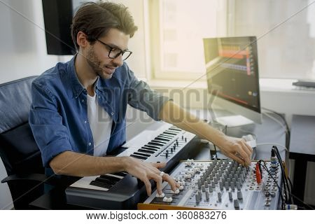 Music Producer Is Composing A Song On Synthesizer Keyboard And Computer In Recording Studio. Man Is
