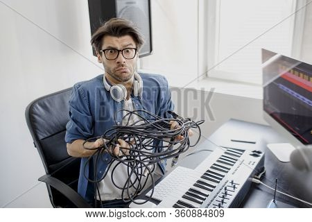 Doesnt Know What To Do With Wires And Cords And Cables. Dj In Broadcasting Studio. Music Producer Is