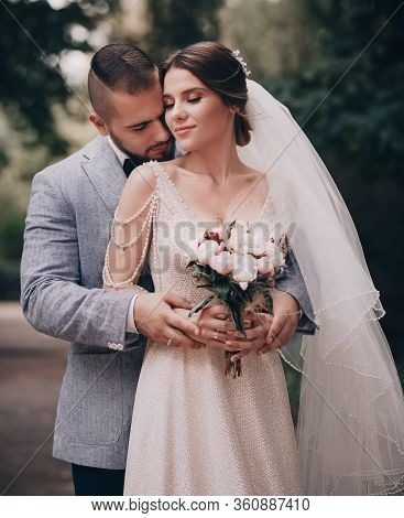 Bride And Groom At Wedding Day Walking Outdoors On Spring Nature. Loving Wedding Couple Outdoor.
