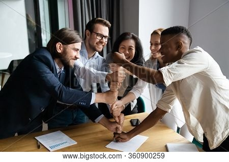 Overjoyed Multiethnic Businesspeople Stack Fists Engaged In Teambuilding