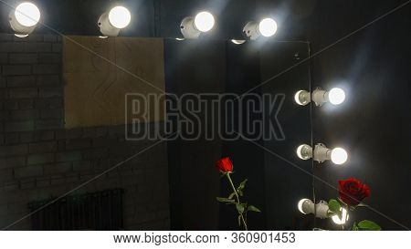 Reflection Of Red Rose In Makeup Mirror On Black Background. Vain Concept. Light Bulbs Around The Pe