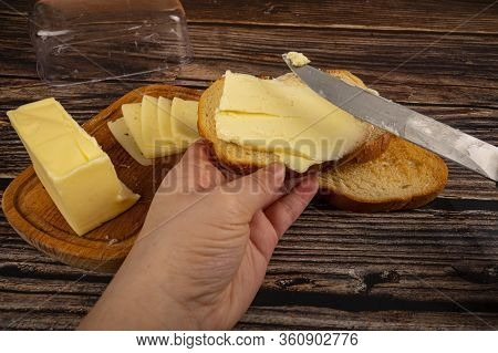 Someone Spreads Butter On Fresh Wheat Toast With A Knife And A Wooden Butter Dish With A Piece Of Bu