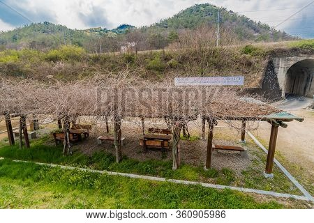 Hwanggan, South Korea; April 10, 2020: Covered Picnic Tables In Front Of Arched Bridge And Sign Of T