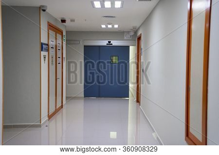 A Huge Blue Door In A White Corridor In A Hospital.