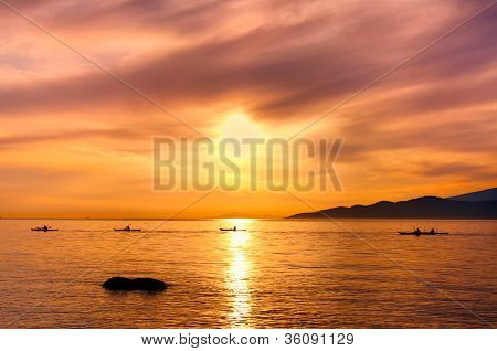 Kayakers Silhouette On Ocean During Orange Sunset