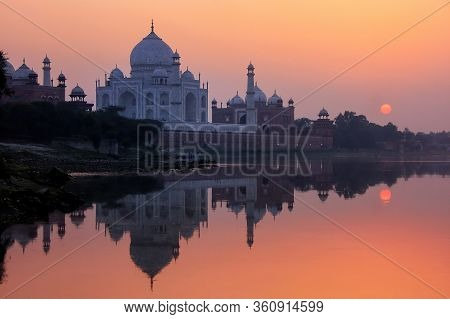Taj Mahal Reflected In Yamuna River At Sunset In Agra, India. It Was Commissioned In 1632 By The Mug