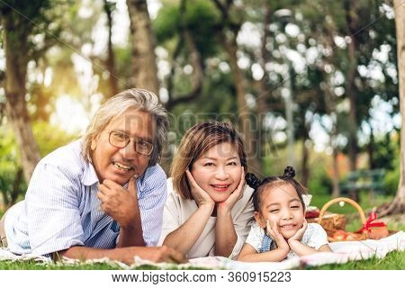 Portrait Of Happy Grandfather With Grandmother And Little Cute Girl Enjoy Relax Looking At Camara In