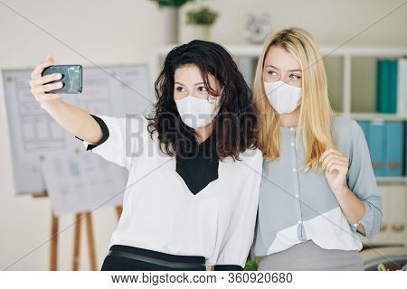 Pretty Young Businesswoman In Medical Mask Working In Office During Pandemic Period And Taking Selfi