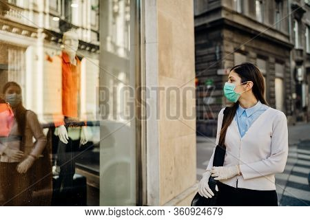 Woman With Mask Looking At A Closed Fashion Clothes Storefront.clothing Shopping During Coronavirus