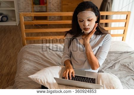 Portrait Of Young Asian Girl Applying Facial Mask On Her Face While Using Computer Laptop In Bedroom