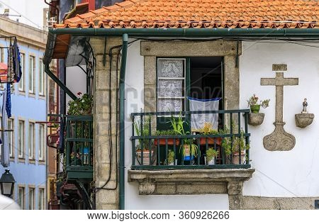 View Of The Shabby Facades And Terracotta Roofs Of Traditional Portuguese Houses With Flower Pots In