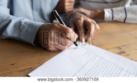 Close Up Older Man Putting Signature On Legal Documents