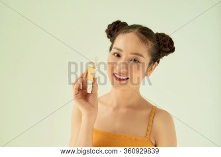 Young Beautiful Asian Woman Showing Hand Sanitiser Against Light Background.