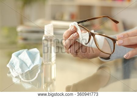 Close Up Of Woman Hand With Protective Mask Cleaning Eye Glasses With Sanitizer And Cloth Sitting On