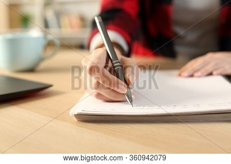 Close Up Of Student Girl Hands Writing Notes On Notebook At Home Sitting On A Desk