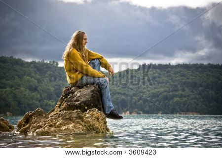 Young Man Sitting On A Rock Near A Sea