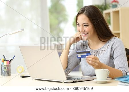 Happy Woman Paying Online With Credit Card On Laptop On A Desk At Home