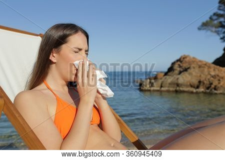 Sick Tourist Woman Blowing Nose With Tissue Sitting On A Deck Chair On A Beach