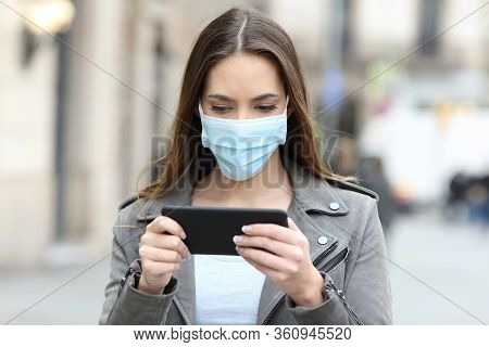 Serious Woman With Protective Mask Avoiding Contagion Watching Video Online On Smart Phone In The St