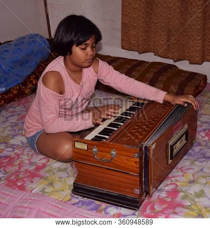 Delhi - India 11th April 2020 An Indian Child Playing Harmonium, A Musical Instrument