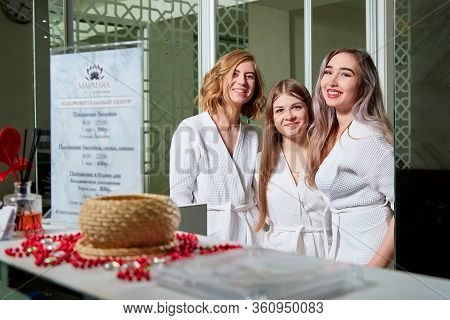 Kirov, Russia - February 25, 2019: Three Nice Young Women In White Bathrobes Standing Near Reception