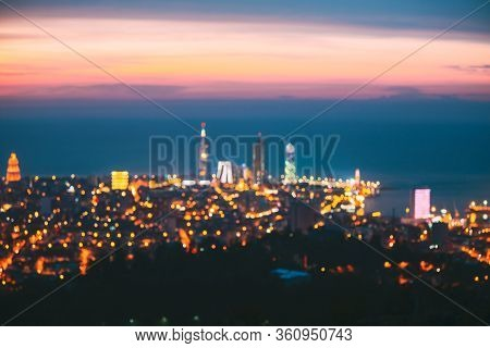 Abstract Natural Blurred Bokeh Boke Background Of Illuminated Cityscape With Skyscrapers And Modern