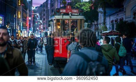 Istanbul, Turkey - November 2019: Taksim Tunel Nostalgia Tram Drives Along Istiklal Street And Peopl
