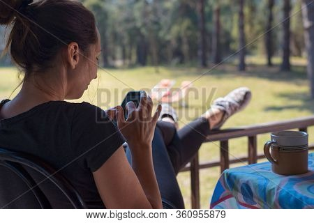 Woman Looking At Cell Phone.vacation Lifestyle. Woman In Vacation Looking At Cell Phone Message.woma