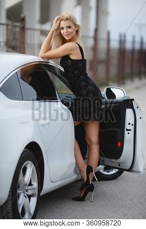 The Elegant Blonde Beautiful Woman Posing Near Luxury Vehicle. Beautiful Young Woman With White Luxu
