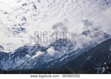 Snowy Peaks Of The Dolomites With Clouds And Pine Woods Around The Lake Of Dobbiaco In The Dolomites
