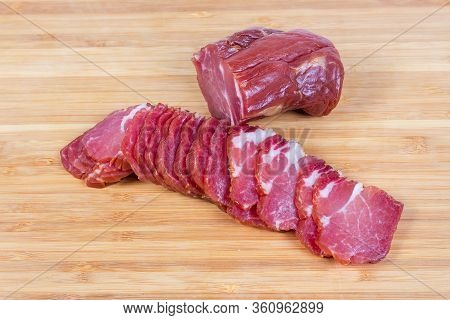 Sliced Air-cured And Smoked Pork Neck And Unsliced Rest Of The Piece On The Bamboo Wooden Cutting Bo
