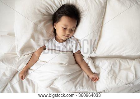Vietnamese Little Girl Sleeping Under Warm Duvet In Bedroom