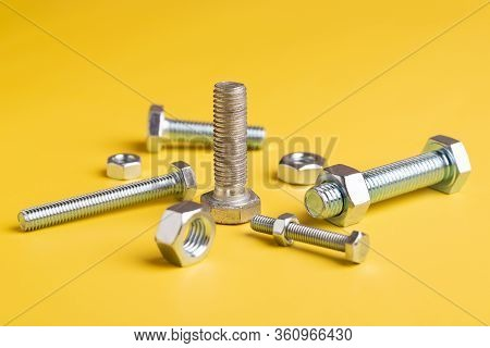 Bolts And Nuts Close-up On A Yellow Background. Still Life Of Metal Nuts And Bolts.
