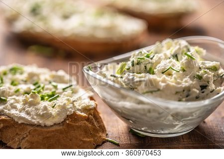 Closeup Of A Bowl Of Homemade Cream Cheese Spread With Chopped Chives Surrounded By Bread Slices Wit