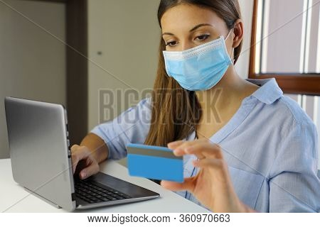 Covid-19 Pandemic Coronavirus E-commerce Mask Girl Buying With Laptop. Young Woman With Mask Buying