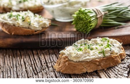 Slices Of Crusty Bread With A Cream Cheese Spread And Freshly Cut Chives On A Vintage Wooden Cutting