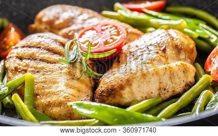 Close Up Of Juicy Chicken Breasts, Spring Peas, Green Beans And Cherry Tomatoes In A Skillet With Bl