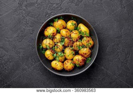Jeera Aloo In Black Bowl On Dark Slate Background. Jeera Aloo Is Indian Cuisine Dish With Baby Potat