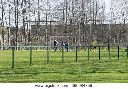Belgium, Sint Gillis Waas, 24 March 2020, Belgian Police Talking To Two Boys Playing On Preserving S