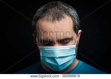 Sad Man With Medical Mask On Black Background. Man Looking Down